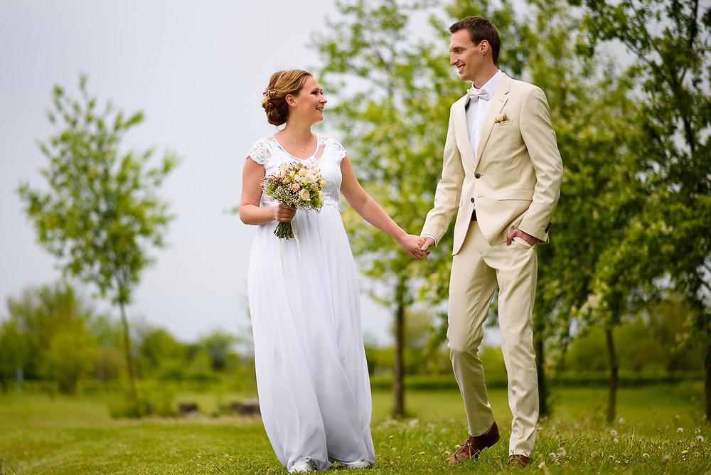 Těhotná nevěsta a ženich v bílém sdílí pohled při procházce u rybníka Prachárna v Olomouci.