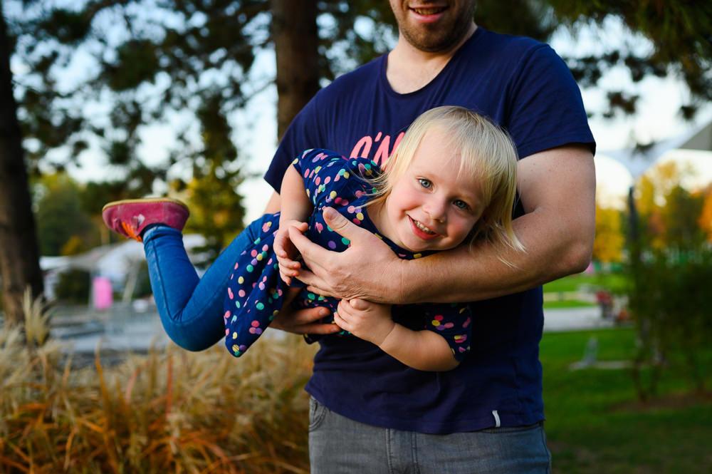 Táta drží dceru při rodinném focení v parku v Olomouci.