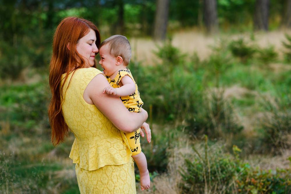 Máma a syn ve žlutém oblečení pózují v lese.