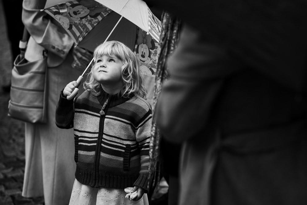 Dívka pod deštníkem se dívá k deštivé obloze před katedrálou svatého Václava v Olomouci.