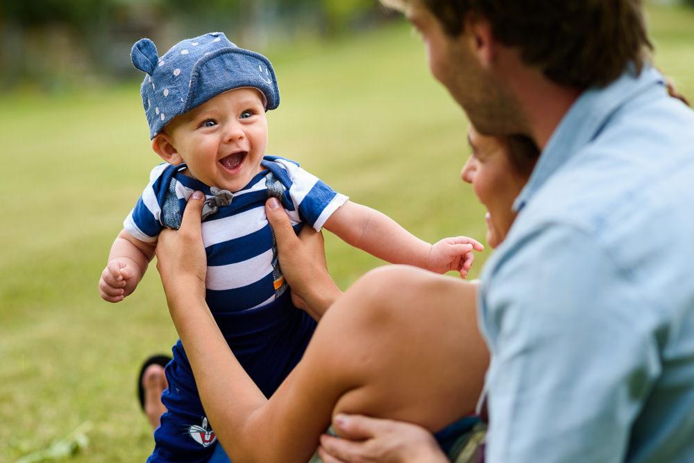 Malý roztomilý chlapec se směje na rodiče při rodinném focení.