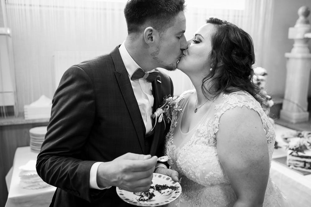 Ženich s nevěstou po rozkrojení dortu ochutnávají a sdílí polibek.