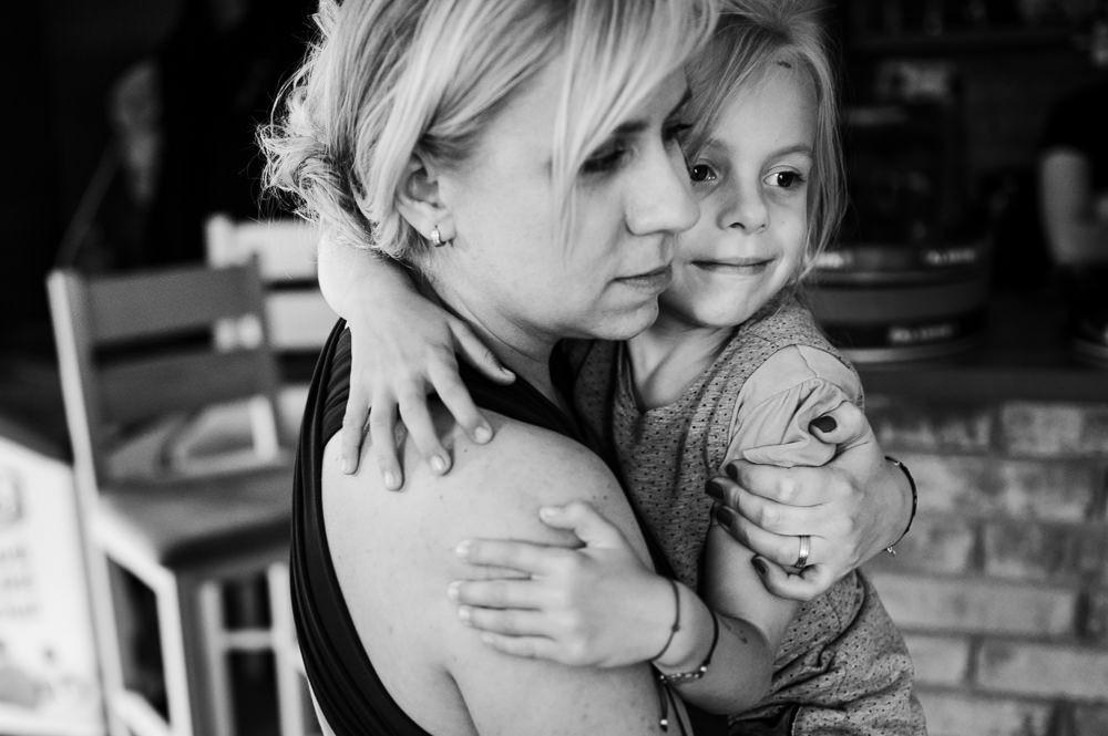 Holčička objímá svou mámu na svatbě rodinné kamarádky.