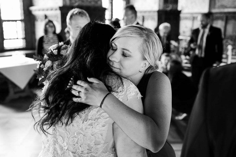 Svědkyně objímá nevěstu po obřadu v rytířském sále na hradě Bouzov.