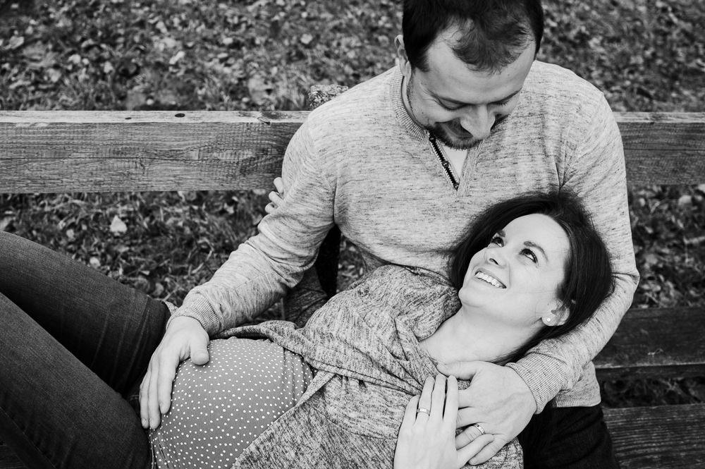 Muž objímá svou ženu a budoucí dítě při těhotenském focení v Olomouci.