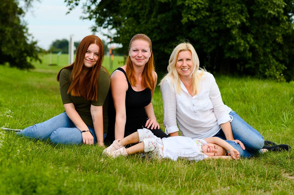 Portrét tří sester a jejich mámy venku na trávě.