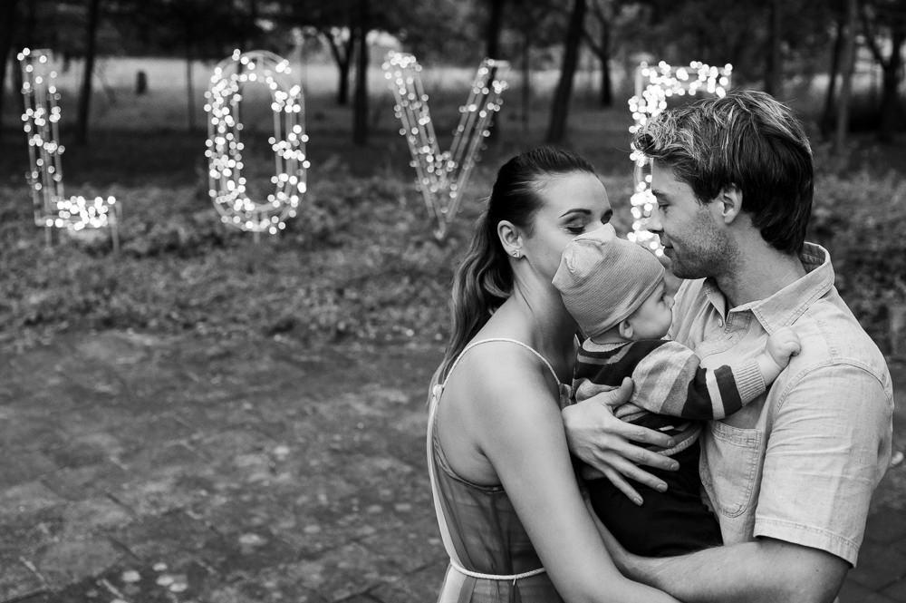 Momentka rodiny na svatbě s nápisem LOVE v pozadí.