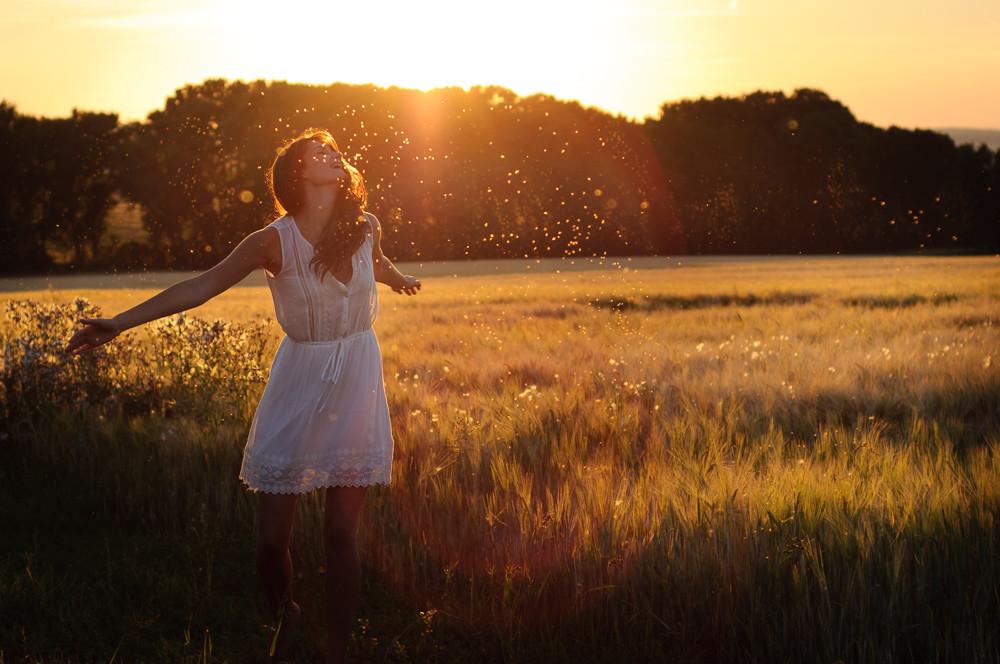 Radost z maličkostí. Žena tančí v obilném poli při západu slunce.