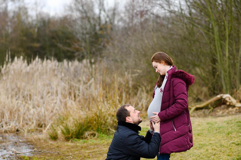 Nastávající táta drží svou těhotnou partnerku za bříško a přitom se na ni dívá.