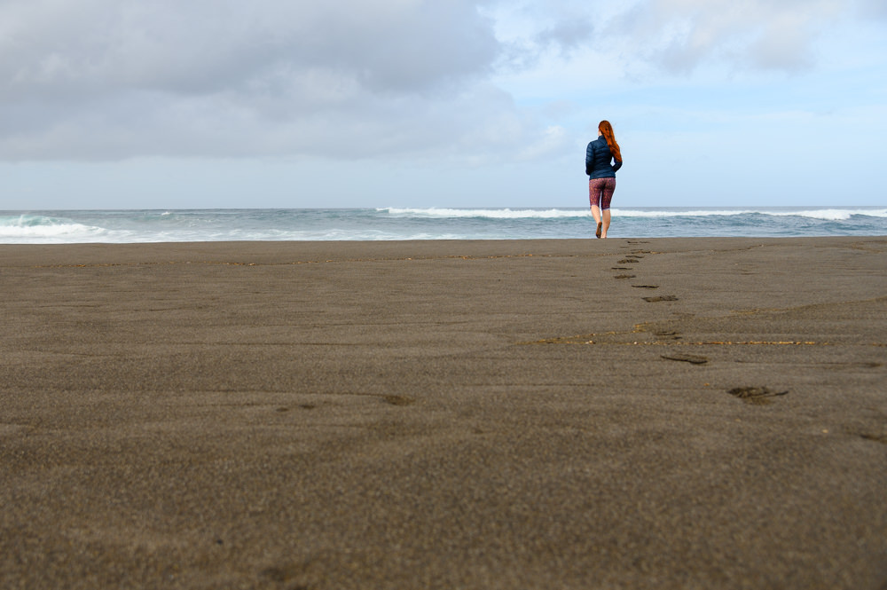A girl is walking on a sand beach in Azores.