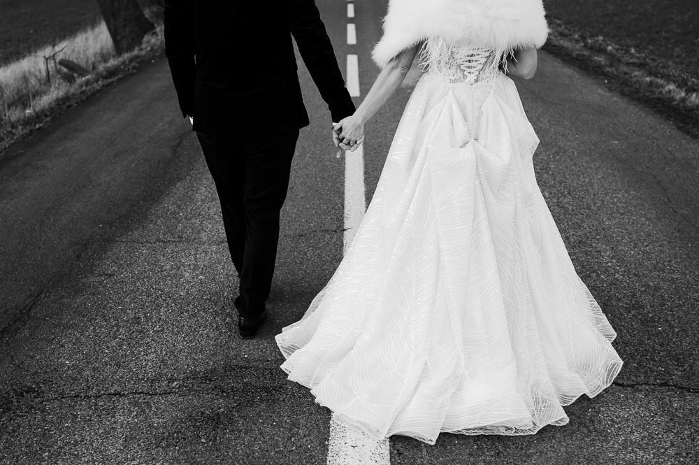 Ženich s nevěstou kráčí ruku v ruce.