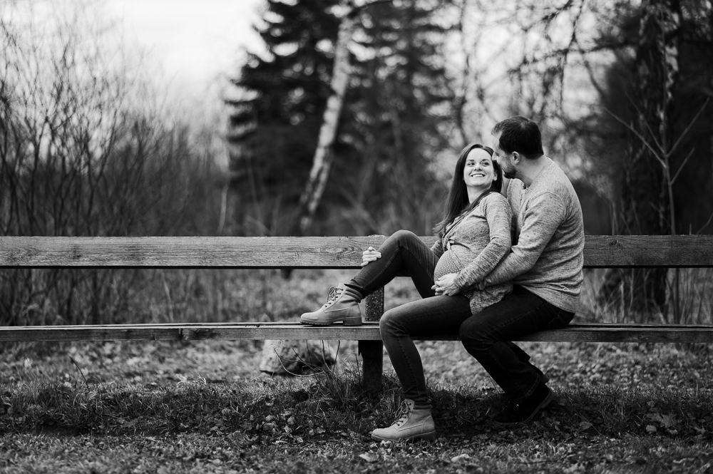 Pár při těhotenském focení se na sebe dívá na lavičce na Poděbradech.