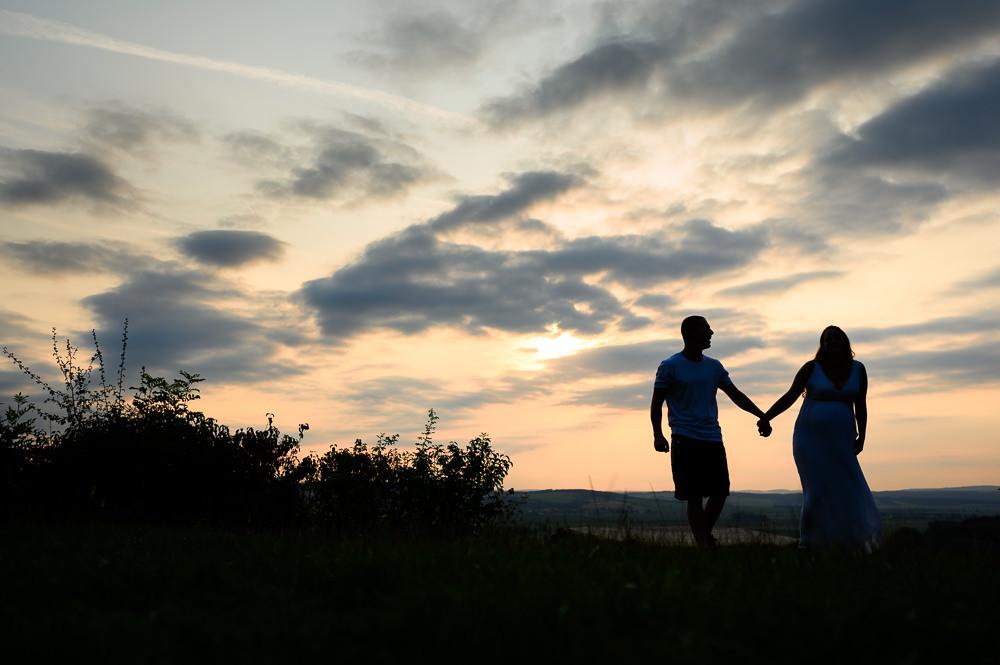 Mladý pár čekající miminko při focení za západu slunce.