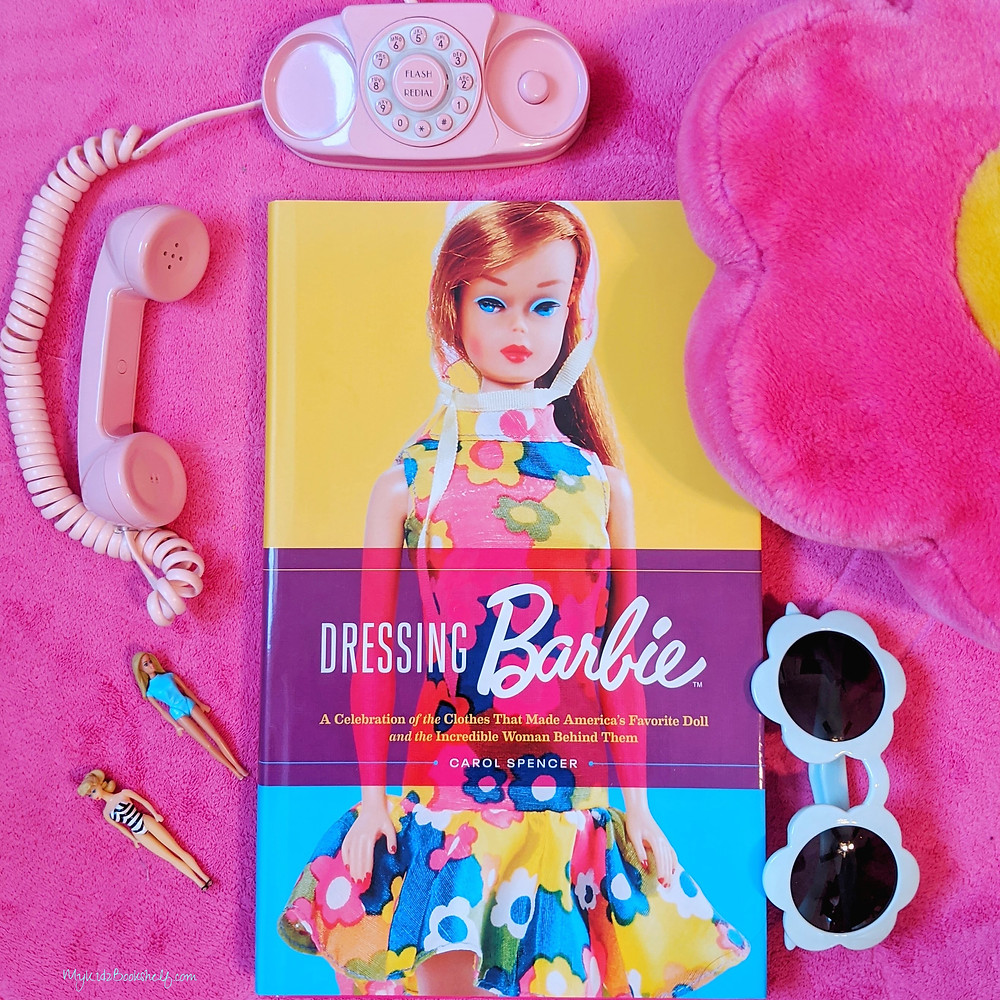 Picture of book Dressing Barbie by Carol Spencer with mini Barbies, sunglasses, pink princess telephone and diasy pillow surrounding the book