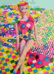 picture of Barbie by Mattel with multicolored geometric patter short set with colorful flower patterned background. Barbie doll has multicolored hair