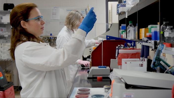 Scientist holds up lab sample.png