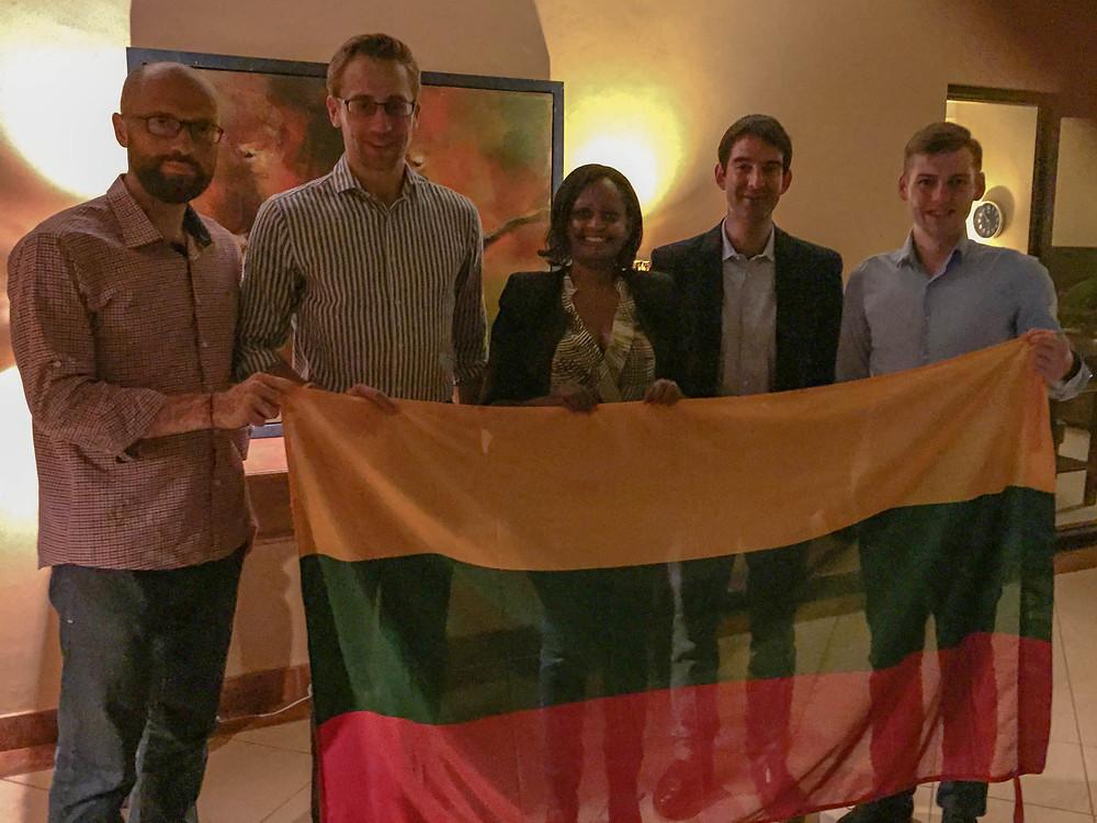 From right to left: Mr. Dalius Budvytis, Mr. Tomas Montvilas, Mrs. Jeanne Kasente Mpobusingye (Consular Executive), Honorary Consul Hrishikesa Madhvani, and Mr. Arnas Petravičius standing with the Lithuanian Flag.