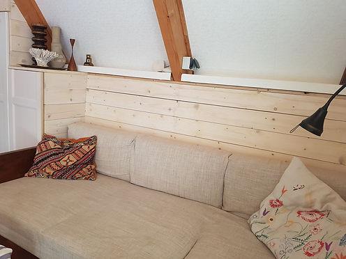 návrhy interiéru dřevěná chata pohovka vyšívaný polštář dekorace korál svícen hygge scandi