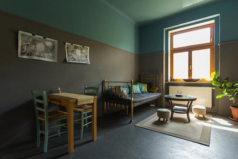 návrhy interiéru obývací pokoj mosazná postel tmavý šedá petrolejová mosazná postel kulatý stolek fíkus