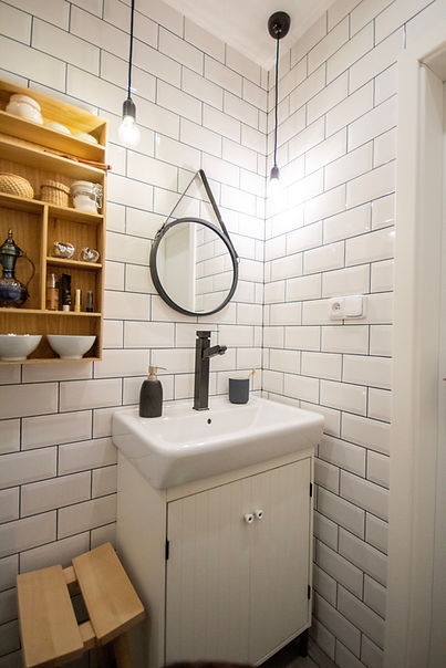 interior design czech prague white bathroom black faucet tap subway tiles round mirror wooden accessories styling bare bulb