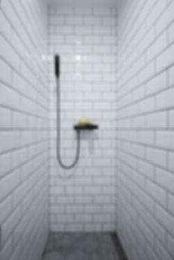 interior design czech prague white bahroom subway tiles shower grey porcelain hexagon tiles black tap faucet sponge