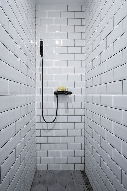 interior design czech prague white bahroom subway tiles shower grey porcelain hexagon tiles black tap faucet sponge