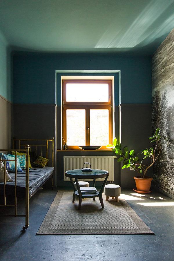 návrhy interiéru obývací pokoj mosazná postel tmavý šedá petrolejová  kulatý stolek fíkus