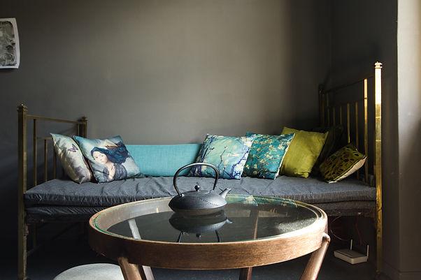 návrhy interiéru mosazná postel polštářky hygge tmavý interiér šedá vintage kulatý stolek útulný dekadentní