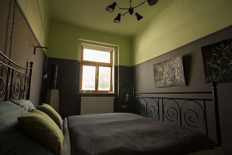 návrhy interiéru ložnice tmavá šedá zelená kovová postel obrazy přehoz