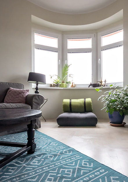 interior design czech prague living room gray sofa teal rug black lamp round table karup armchair futon plant curved bay window