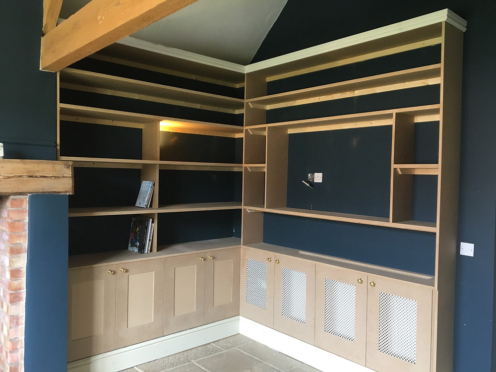 Library with lower level shaker style cupboards, one side vented for  radiator.