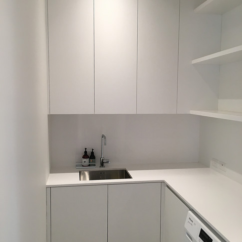 Laundry Under and over bench cabinets with floating shelves.  Caesarstone benchtop.