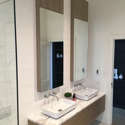 GFL Bathroom vanity and overhead cabinets in Oak with marble benchtop.