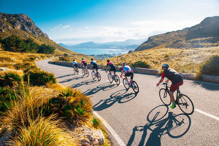 Team sport cyclist photo. Group of triathlete on bicycle ride on the road at Mallorca, Maj