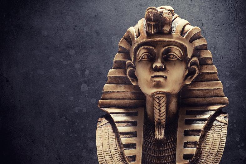 Stone pharaoh tutankhamen mask on dark b