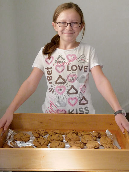 Emily Henegar of Cookie in the Kitchen poses with cookies before starting Cookie in the Kitchen