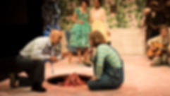 A man and his son, kneeling, talk, while the wife and daugter look on