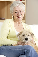 Senior Woman Holding Dog On Sofa.jpg