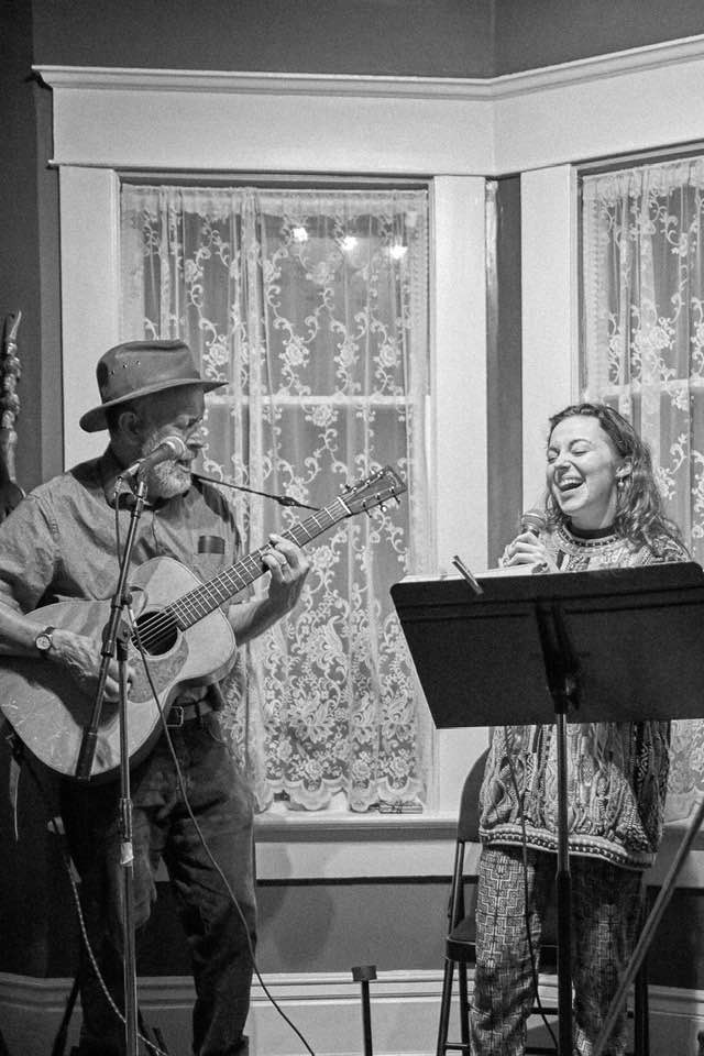 An older man with a fedora plays an acoustic guitar while a young woman sings along