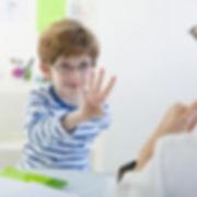 Jeune garçon portant des lunettes montre le chiffre quatre avec ses doigts.