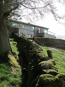Dry stone wall leading up to eco home in Scotland
