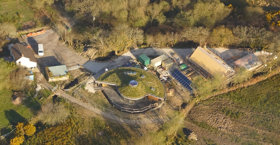 Aerial view of round house with green roof and timber framed barn