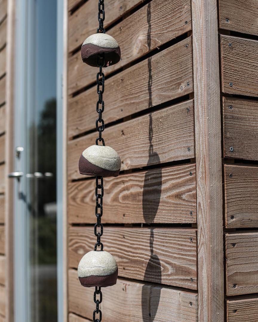 Japanese rain chain against timber cladding