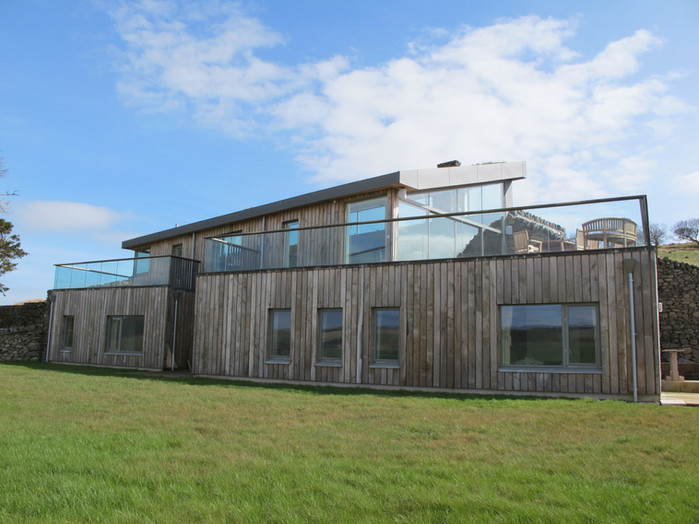 Timber and stone clad eco home with glass balustrades