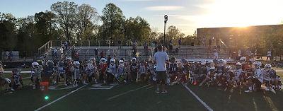 Kids withCoach on Lacrosse Field.jpg