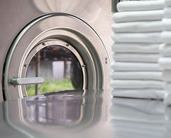 Stack%20of%20clean%20bed%20sheets%20in%20front%20of%20industrial%20washing%20machine.%20Fo