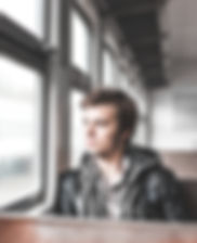 photo-of-man-sitting-in-train-looking-ou