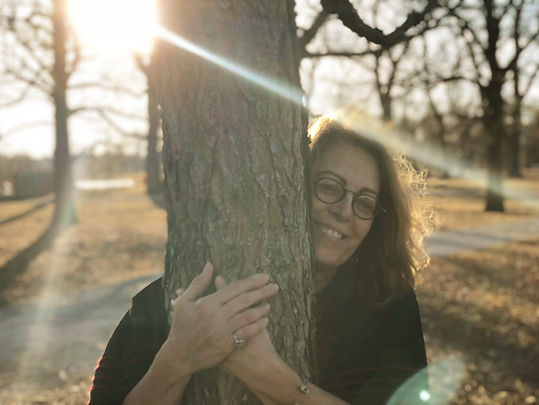 Susan Brockmeier in nature with trees and bright rays of sunlight streaming down.