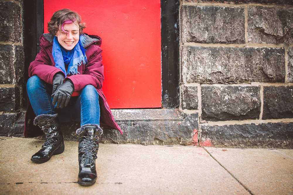 Sarah Blake by JPG Photography. Author of Mr. West,  Let's Not Live on Earth and Naamah. Brick wall, red door, jeans, gloves and boots.