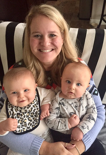 An experience doula taking care of smiling twins